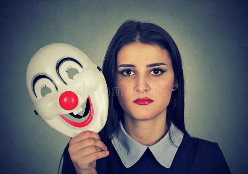 Sad woman holding clown mask expressing cheerfulness happiness. Young woman with sad face expression holding clown mask expressing cheerfulness happiness stock photo