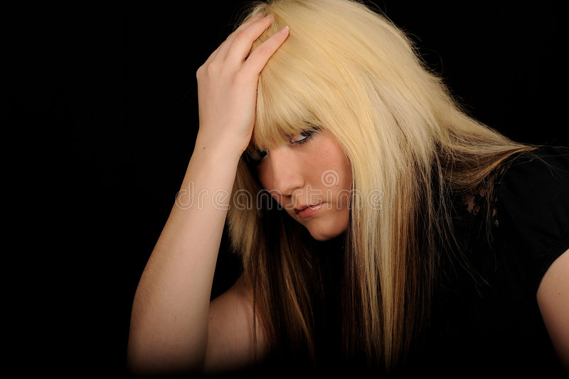 Sad woman holding head. Half body portrait of sad blond haired woman holding head, black background stock photo