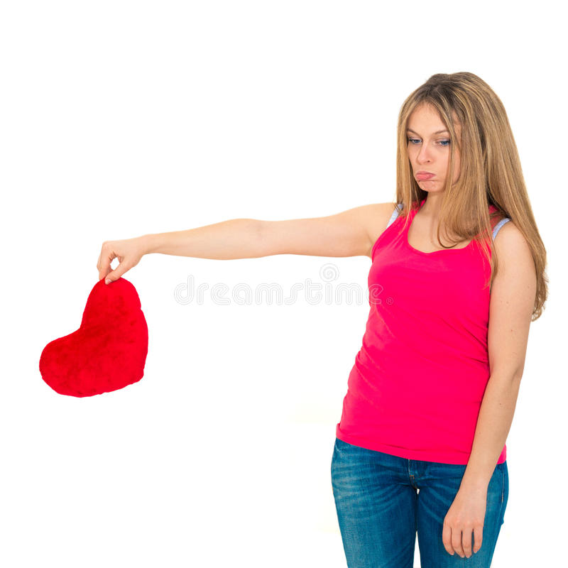 Sad woman holding red valentine heart. Young lonely sad woman holding red valentine heart royalty free stock photo