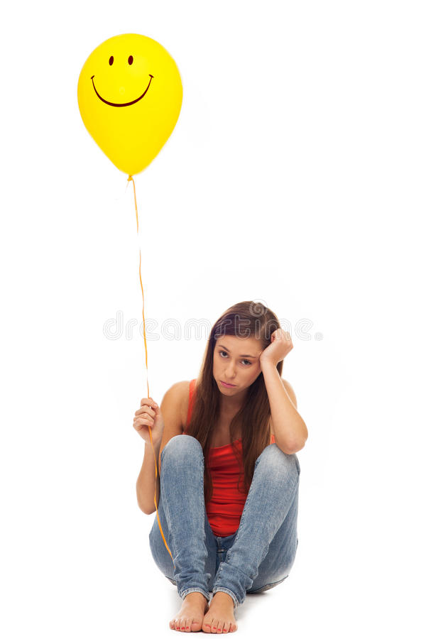 Sad woman holding smiley face balloon stock photos
