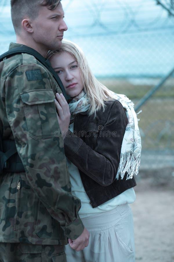 Sad woman hugging military husband royalty free stock images