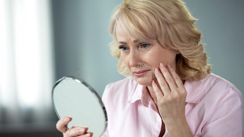 Sad woman looking at face reflection and crying, unhappy with wrinkled skin royalty free stock photo
