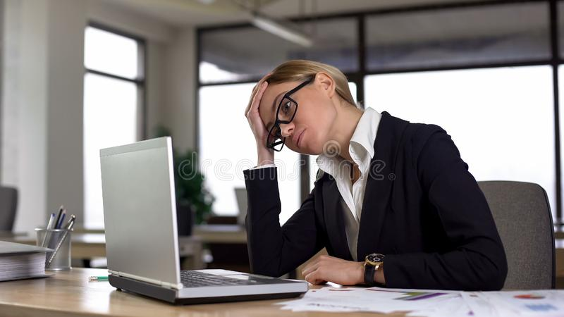 Sad woman looking at laptop, worried about difficult project, lack of experience royalty free stock image