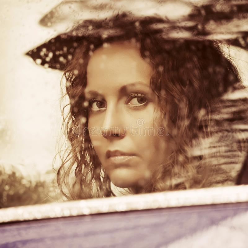 Sad woman looking out car window royalty free stock image