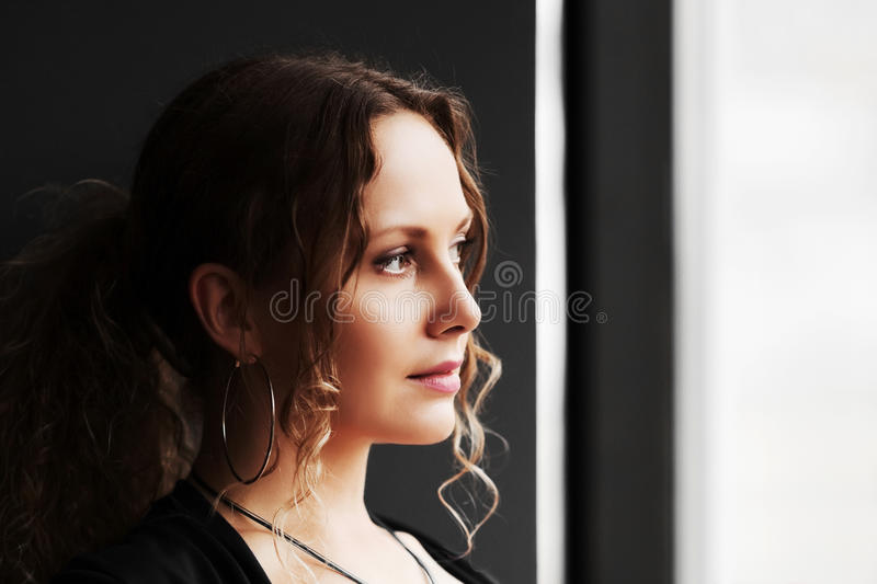 Sad woman looking out the window royalty free stock images