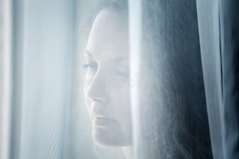 Sad woman looking out window stock images