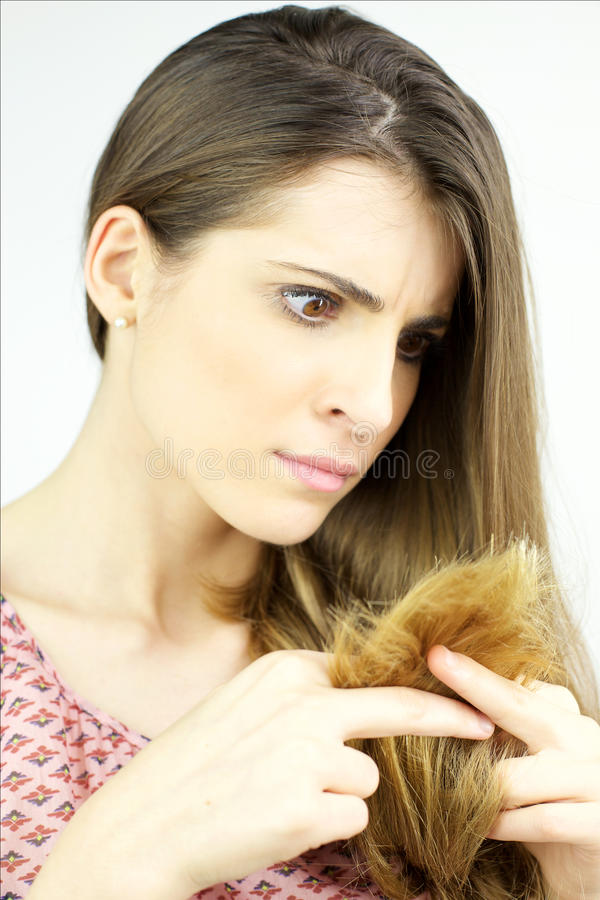 Sad woman looking unhealthy long hair. Woman making funny face looking split ends hair stock photography