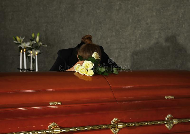 Sad woman mourning near casket with white roses in funeral royalty free stock photography