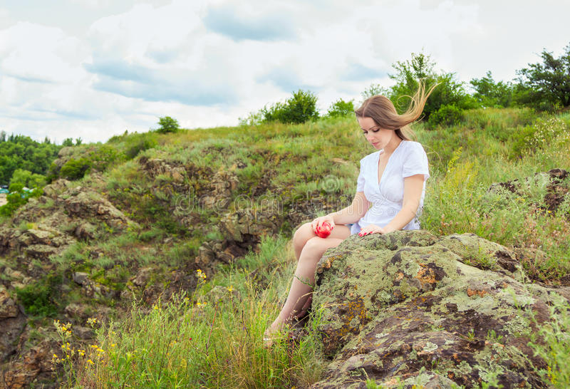 Sad woman with nectarine. Beautiful young sad woman with long hair, waving in the wind, sitting on the rock in the forest holding ripe red nectarine stock photo