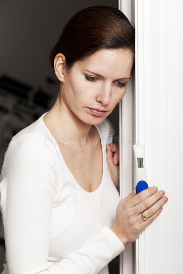 Sad woman with negative pregnancy test royalty free stock photography
