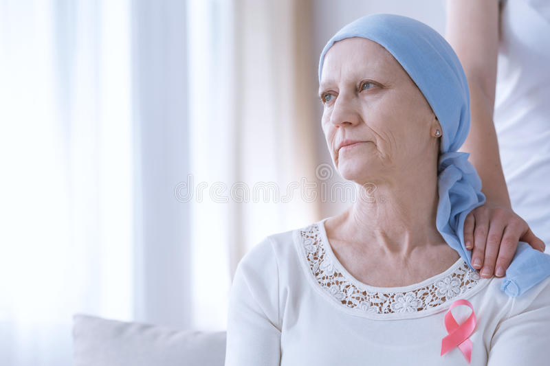 Sad woman with pink ribbon. Sad cancer women with headscarf wearing pink ribbon on chest stock photos