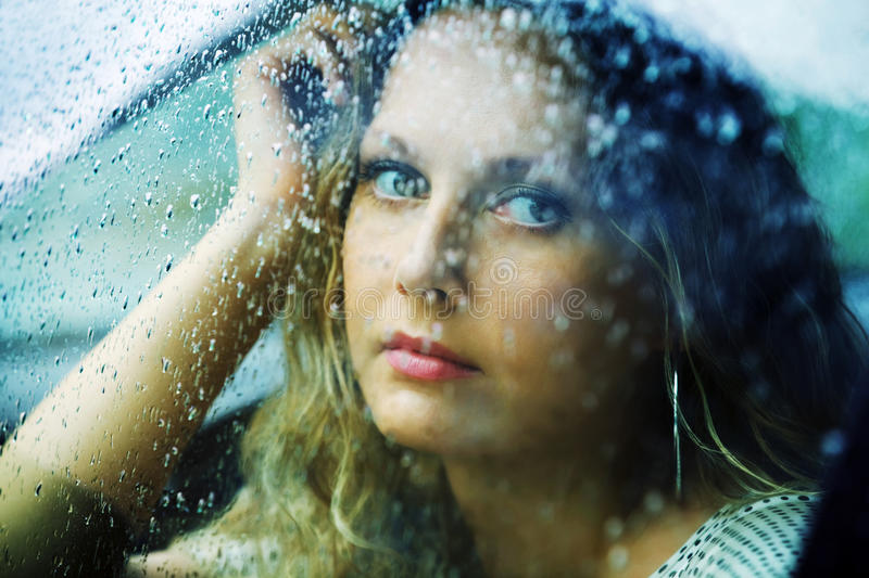 Sad woman in a car in the rain royalty free stock photos