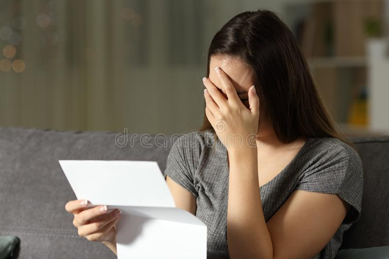 Sad woman reading a letter in the dark. At home stock image