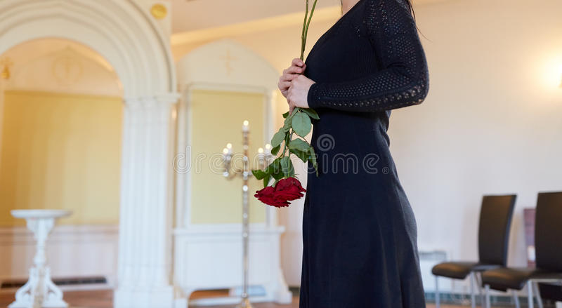 Sad woman with red rose at funeral in church royalty free stock images