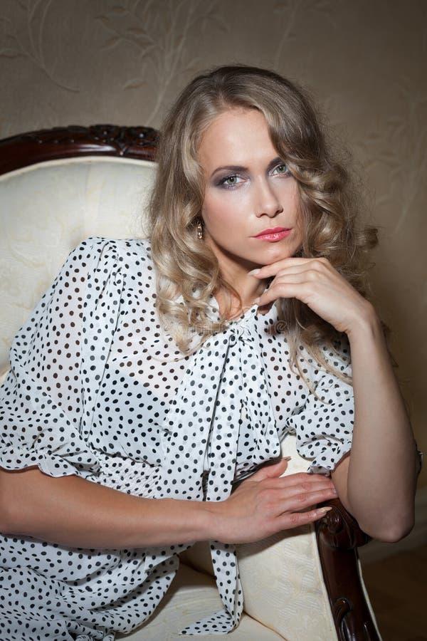 Sad woman in retro style. Sad woman in retro polka dot dress sitting on the coach royalty free stock photography