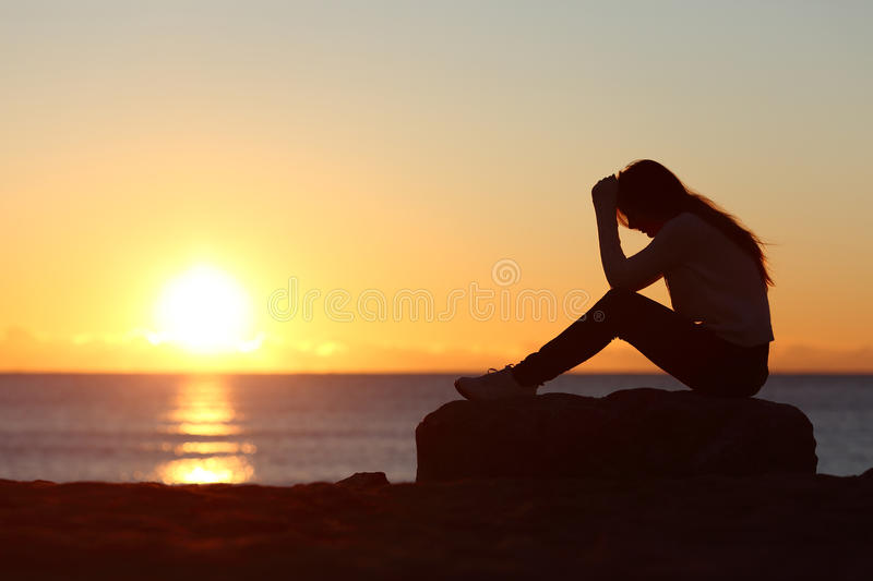 Sad woman silhouette worried on the beach royalty free stock images