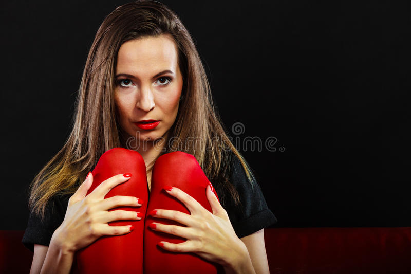 Sad woman sitting on red couch royalty free stock images