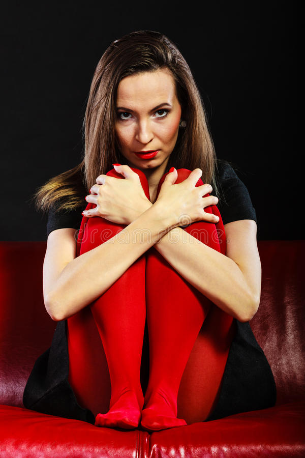 Sad woman sitting on red couch stock photography