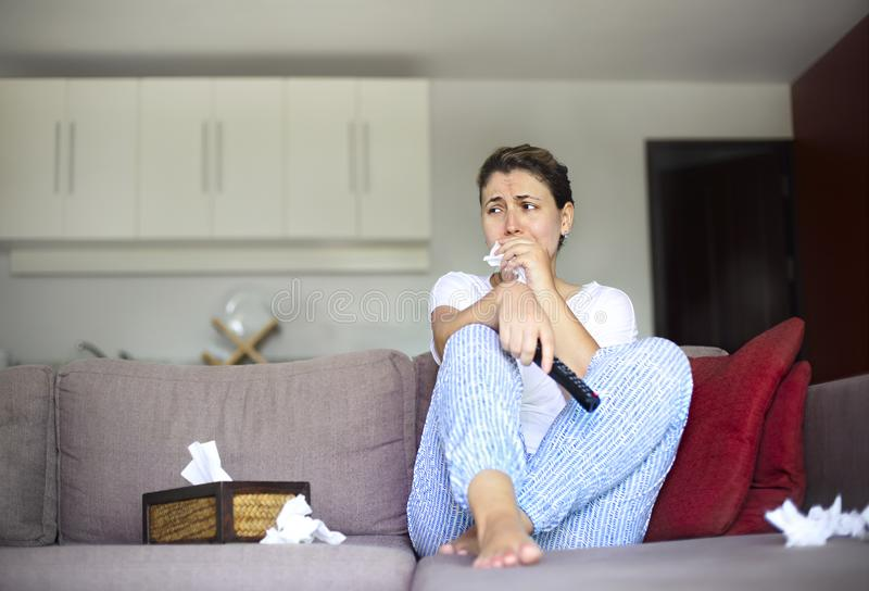 Sad woman sitting on sofa and watching tv at home royalty free stock photo