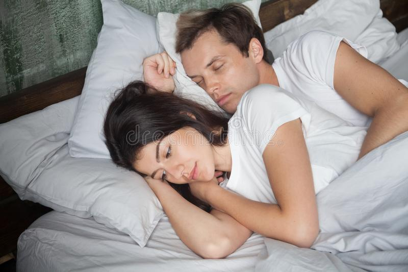 Sad woman and sleeping man lying in bed. Young attractive couple lying in bed under blanket at home. Male sleeping, pensive sad and frustrated female thinking stock photography