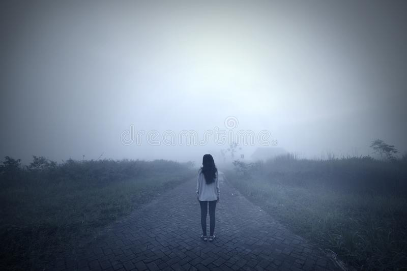 Sad woman standing alone in a misty morning. Back view of a sad woman standing alone in a misty morning. Shot in the mountain stock images