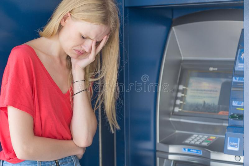 Sad woman standing in front of a ATM bank machine. No money. Distraught young girl is visibly upset in front of the ATM. Her balance is allot lower then it stock photos