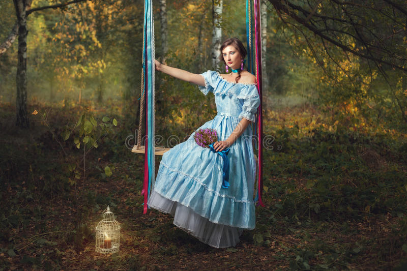 Sad woman on a swing. Sad woman sitting on a swing and holding a bouquet of wildflowers stock photography