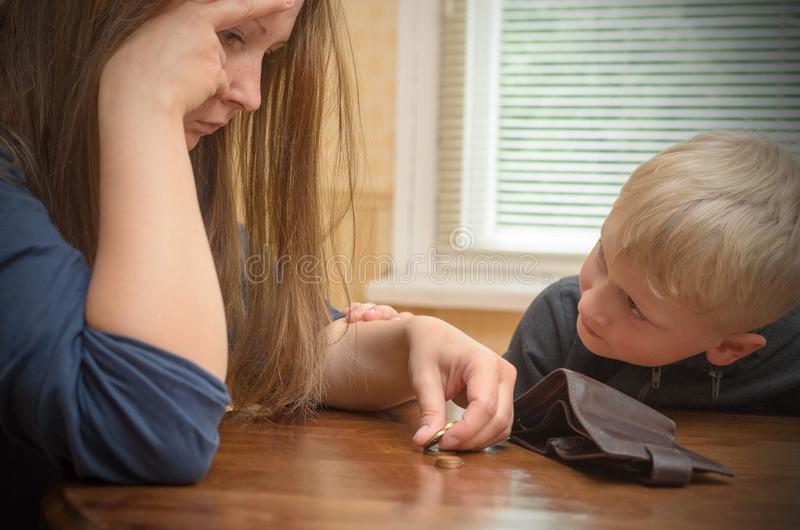 A sad woman at the table thinks the last coins. Empty wallet - boy son calms mother. stock photos