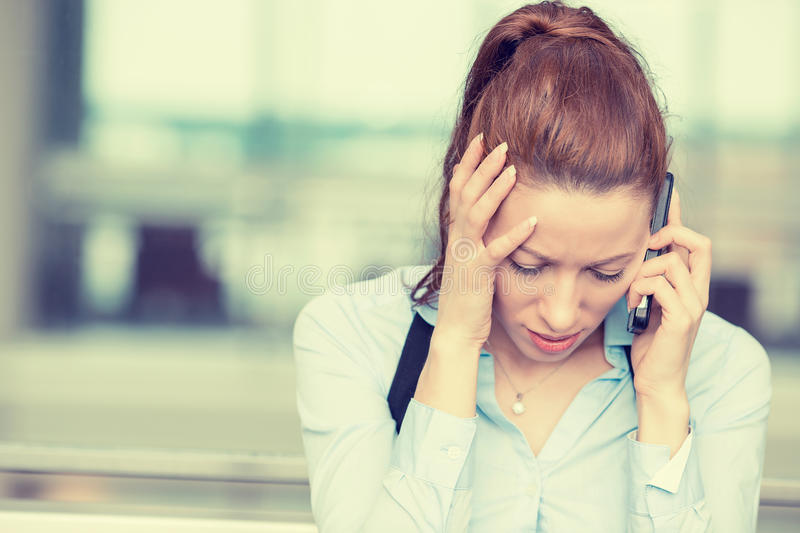 Sad woman talking on mobile phone looking down stock photos