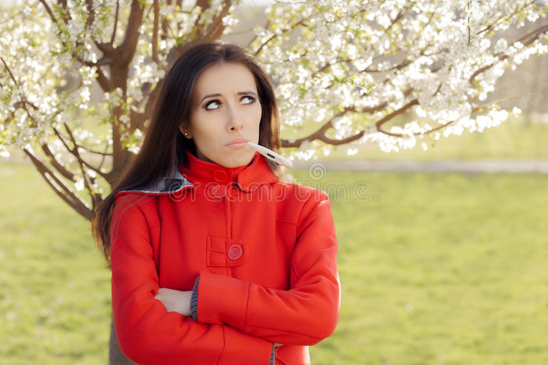 Sad Woman with Thermometer in Spring Blooming Decor royalty free stock images