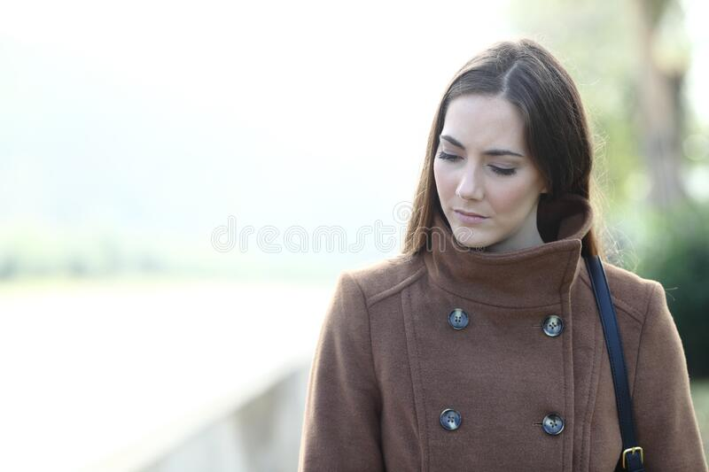 Sad woman walking alone in a park looking down stock photo