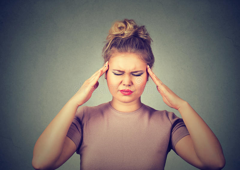 Sad woman with worried stressed face expression looking down trying to concentrate on gray wall background royalty free stock photos