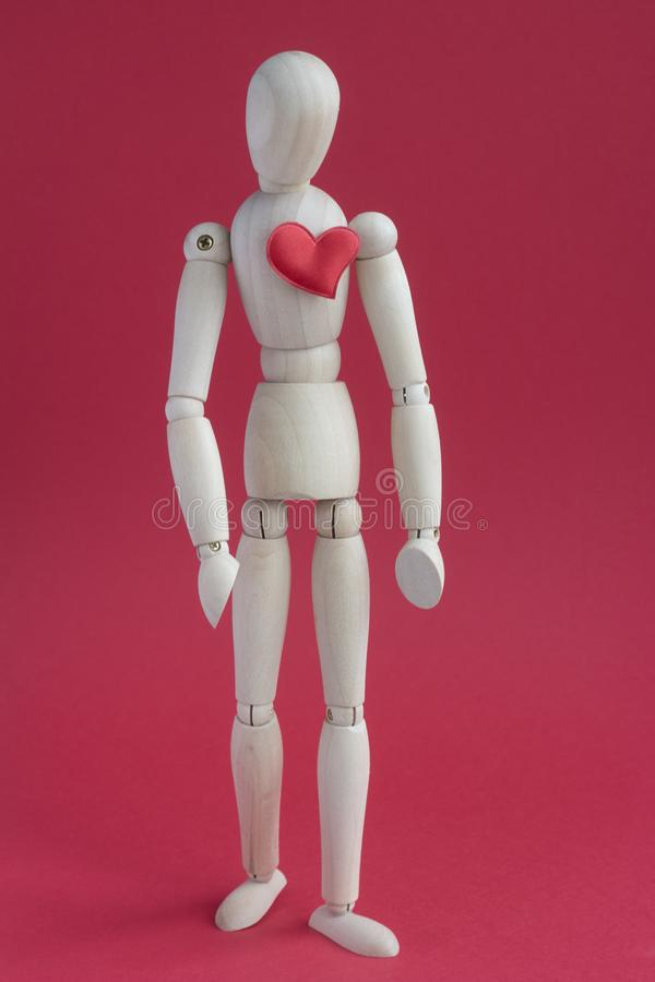 Sad wooden puppet human on red background with small red heart on a breast.  stock photography