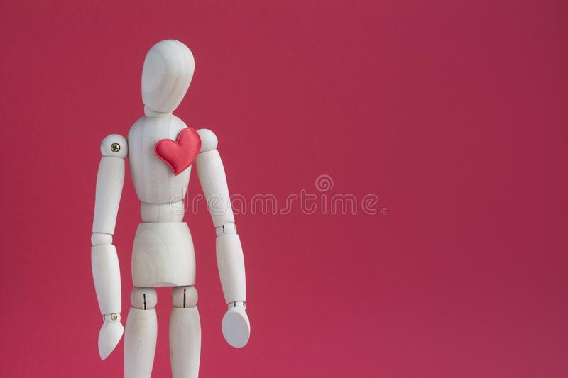 Sad wooden puppet human on red background with small red heart on a breast.  stock photo