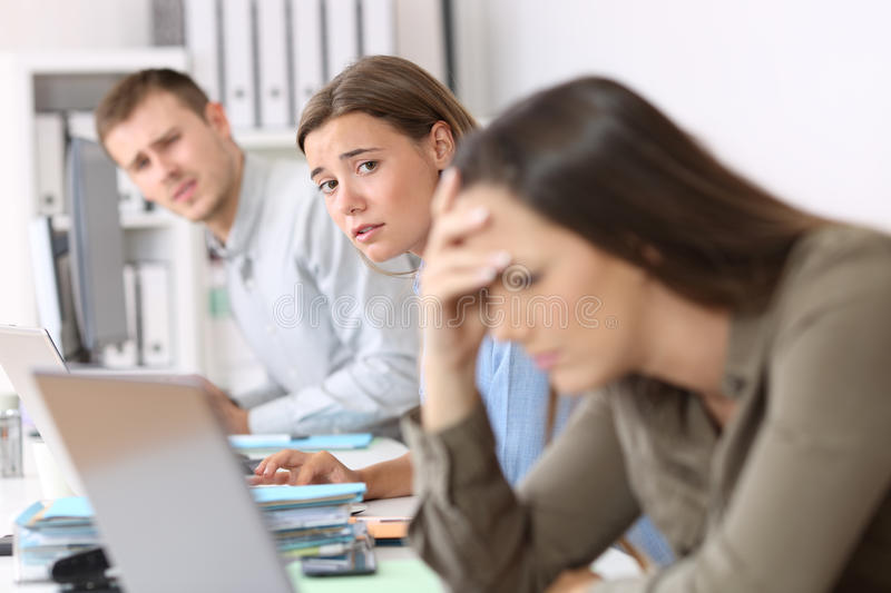 Sad workers looking at a frustrated colleague royalty free stock images