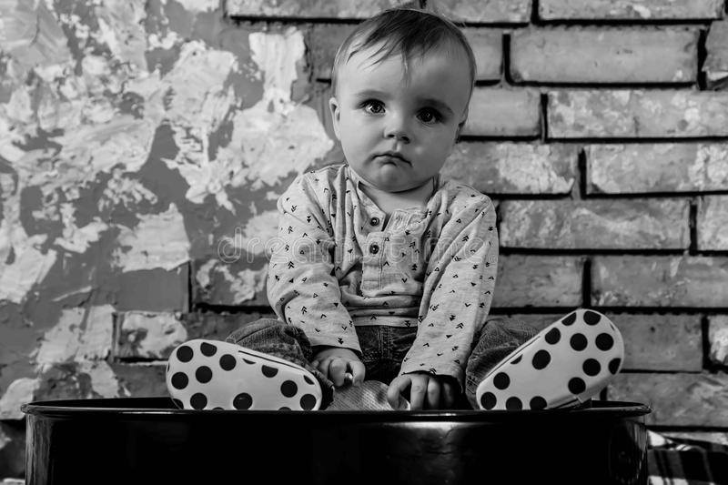 Sad about world problems small child is sitting on a iron barrel Baby boy on the background of a brick wall. Black and white royalty free stock photo