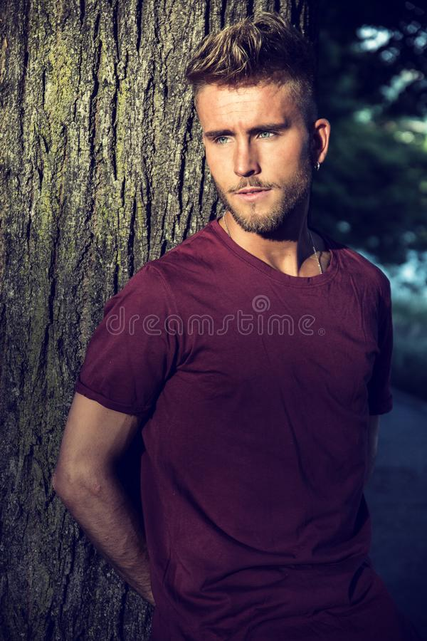Sad, worried blond young man against tree stock photo