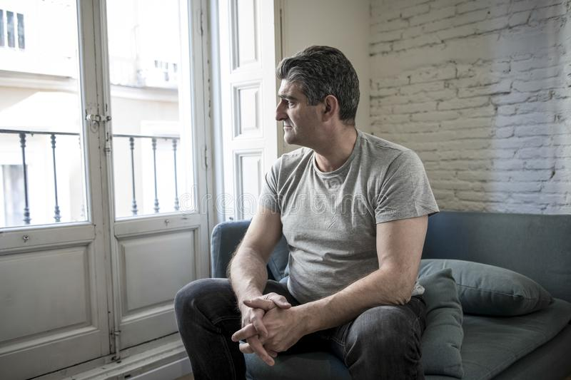 Sad and worried man with grey hair sitting at home couch looking. 40s or 50s sad and worried man with grey hair sitting at home couch looking depressed and royalty free stock images