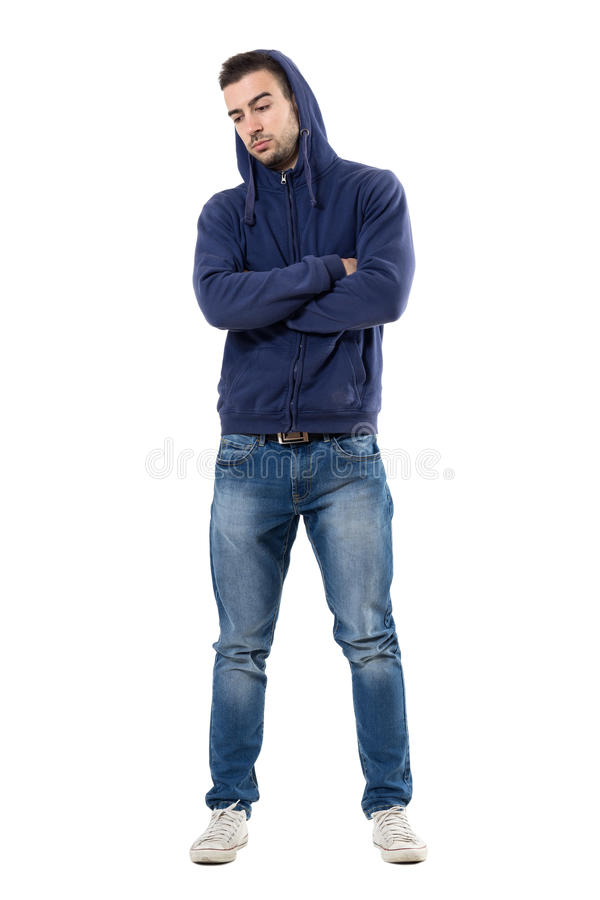 Sad worried young casual man in hoodie with crossed arms looking down stock photo