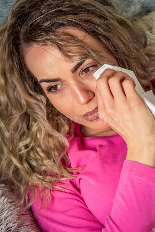 Sad and worried young woman crying alone in bed royalty free stock images