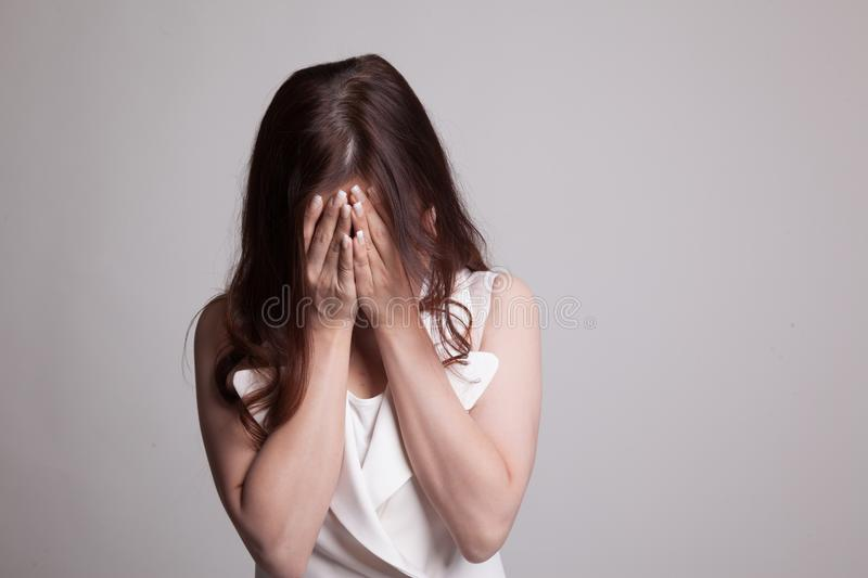 Sad young Asian woman cry with palm to face. Sad young Asian woman cry with palm to face on gray background stock photo