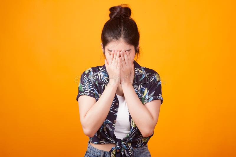 Sad young Asian woman cry with palm to face in tropical shirt. On yellow background stock image