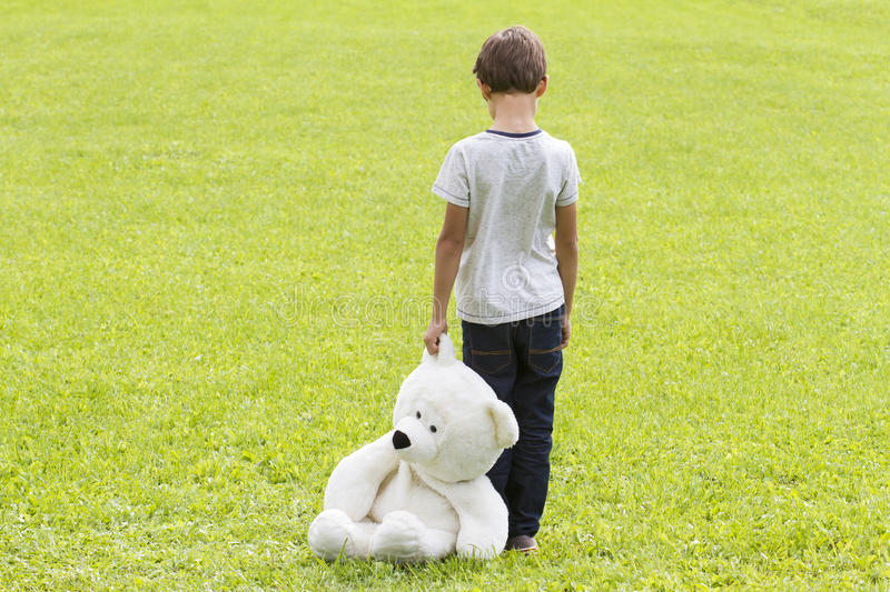 Sad young boy is holding a teddy bear and standing on the meadow. Child looking down. Back view. Sadness, fear royalty free stock photo