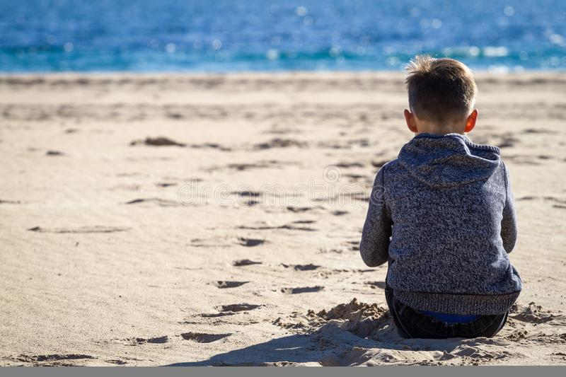 Sad young boy sitting on the beach, looking at sea and thinking stock photo