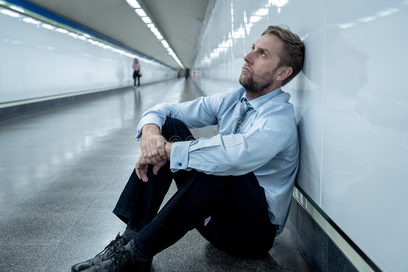 Sad young businessman jobless suffering from depression sitting depressed on ground street subway. Desperate sad young businessman suffering emotional pain grief stock photo