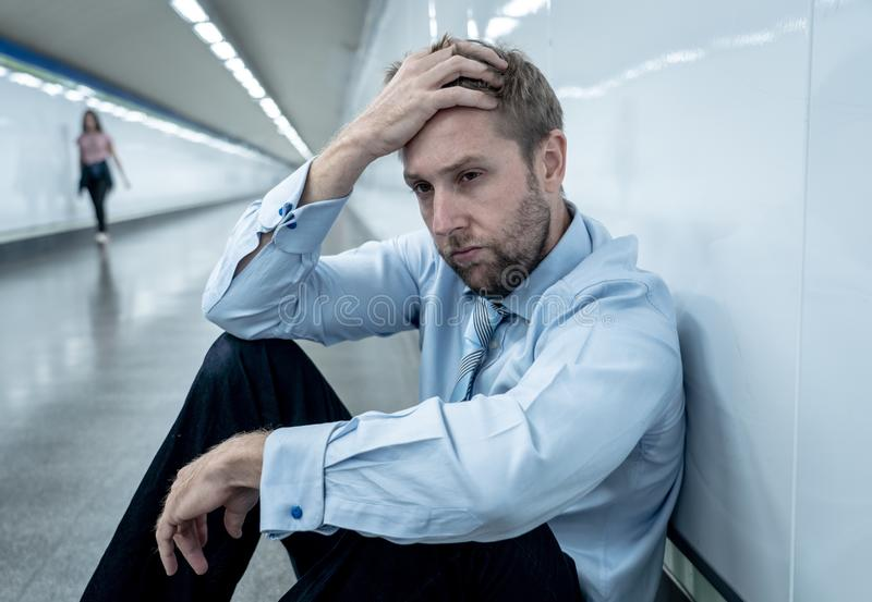Sad young businessman jobless suffering from depression sitting depressed on ground street subway. Desperate sad young businessman suffering emotional pain grief stock images
