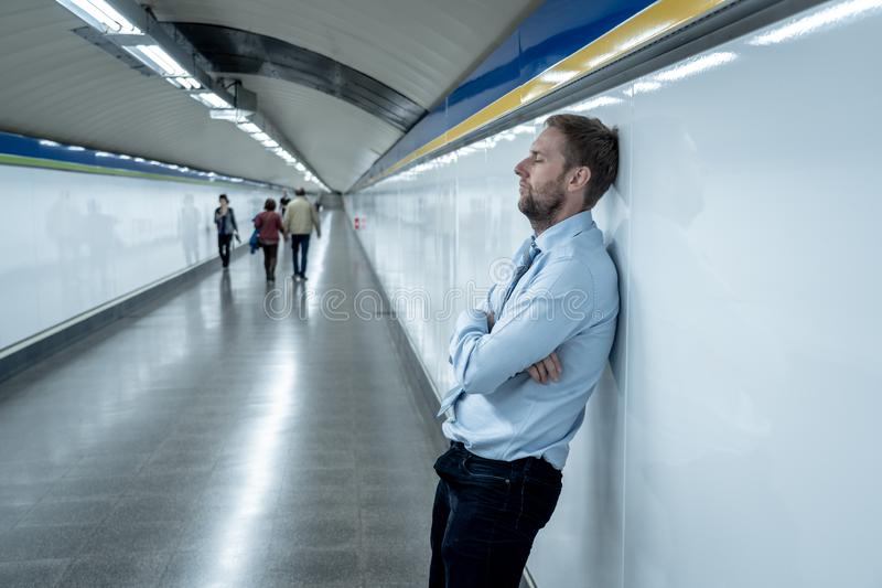 Sad young businessman jobless suffering from depression sitting depressed on ground street subway. Desperate sad young businessman suffering emotional pain grief stock photography