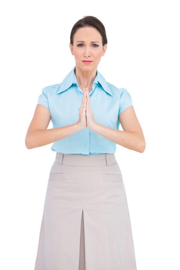 Sad young businesswoman praying. While posing on white background royalty free stock image