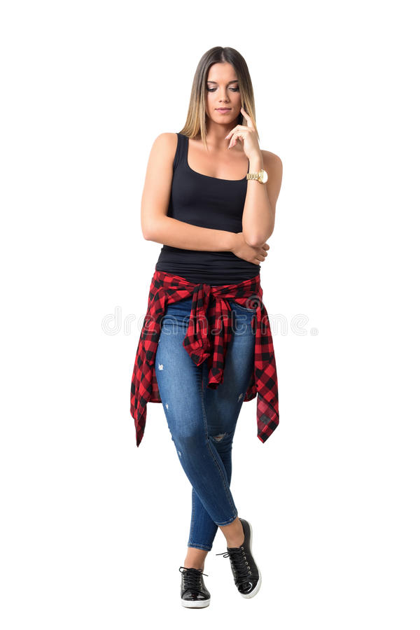 Sad young casual woman in street style clothing looking down stock image