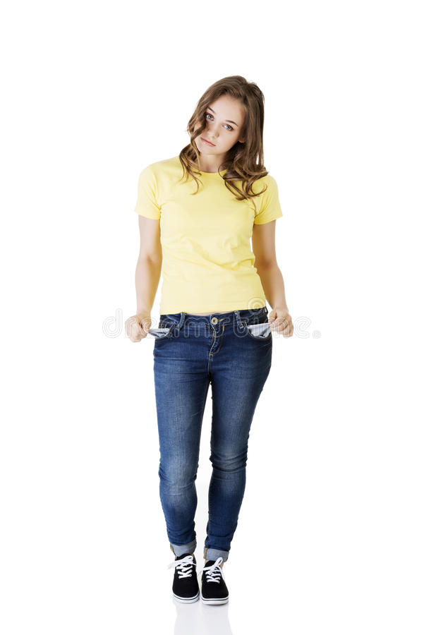 Sad young caucasian teen girl taking out empty pockets royalty free stock image